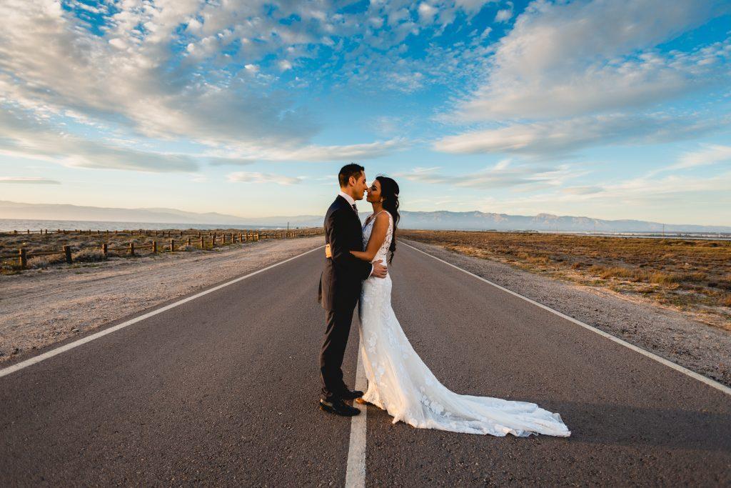 La pareja en su post boda cruzando la carretera de la mejor manera posible.