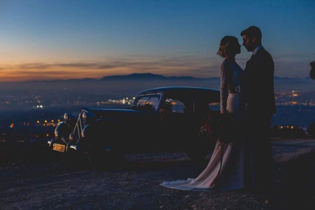 Pareja boda granada al atardecer mirandose con coche de época detras